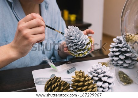 Woman painting pine cones for Christmas  - stock photo