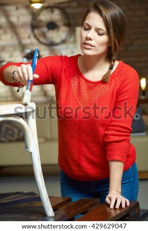 Woman painting, renewing chair at home. - stock photo
