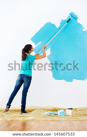 woman painting wall in new home - stock photo