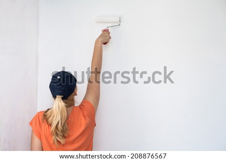 Woman painting white wall with paint roller. - stock photo