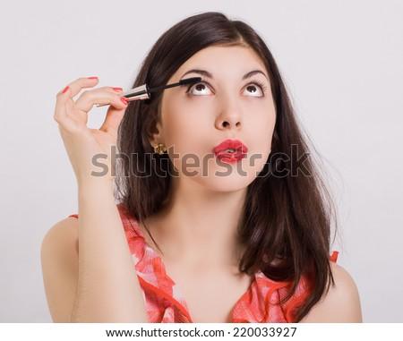 Woman paints eyelashes mascara. - stock photo