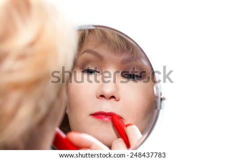 Woman paints her lips red lipstick and looks at herself in the mirror - stock photo