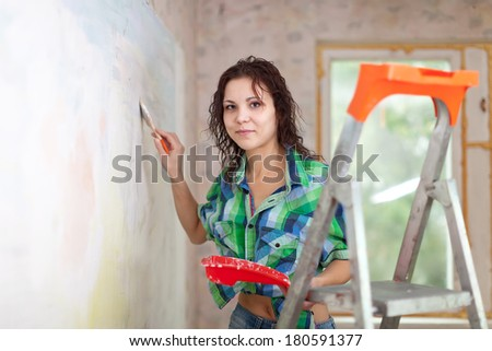woman paints wall with brush at home - stock photo