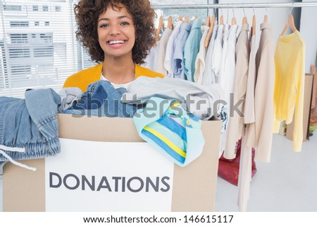 Woman participating at charity and holding donation box - stock photo