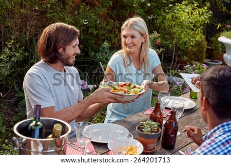 woman passing fresh healthy salad at outdoor friends dinner party gathering - stock photo