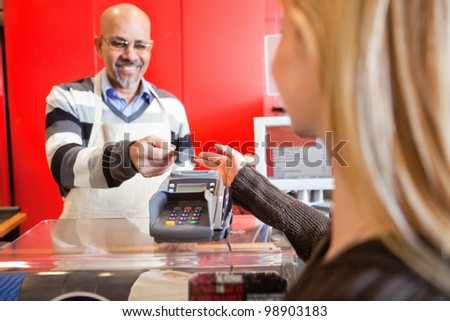 Woman passing over credit card to shop assistant after shopping - stock photo