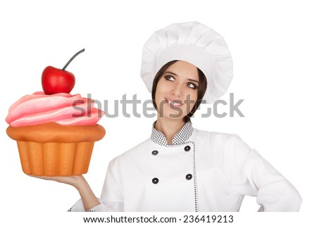 Woman Pastry Chef Holding Huge Cupcake - Portrait of a professional cook presenting a giant baked and decorated muffin  - stock photo