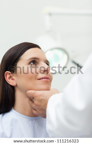 Woman patient being auscultated by a doctor in an examination - stock photo