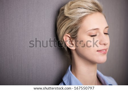 Woman pausing for personal meditation or introspection standing with her eyes closed and a serene expression against a grey background with copyspace - stock photo