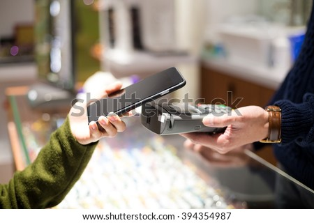 Woman pay by mobile phone in optical shop - stock photo