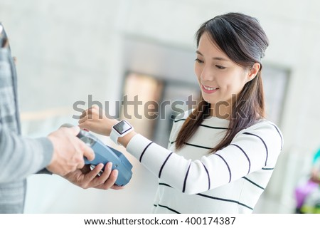 Woman pay by NFC on smartwatch - stock photo