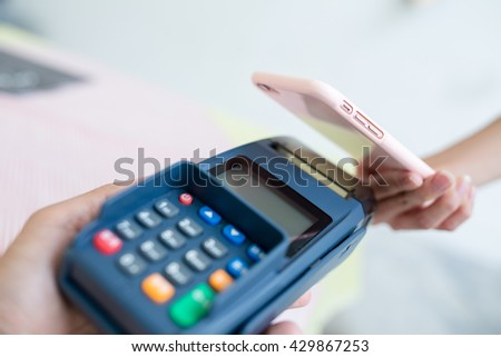 Woman pay with mobile phone by NFC - stock photo