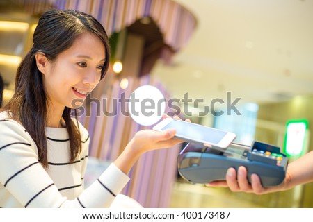 Woman pay with mobile phone by NFC technology - stock photo