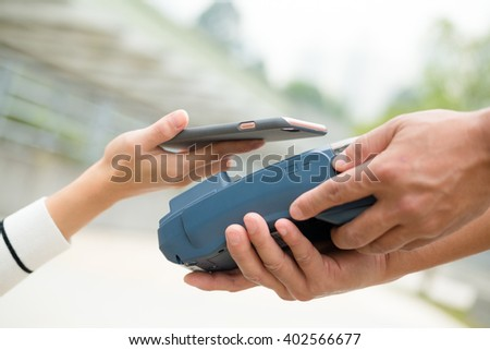 Woman pay with mobile phone with NFC technology - stock photo