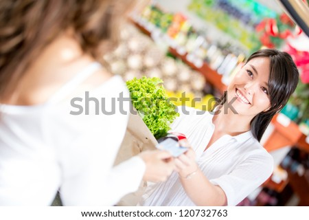 Woman paying at the supermarket with credit card - stock photo