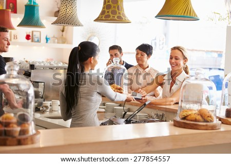 Woman paying for her order in a cafe - stock photo