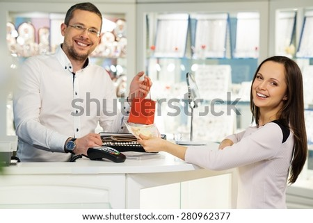 Woman paying with cash in jewellery shop - stock photo