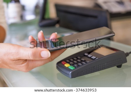 Woman paying with NFC technology on cell phone, beautician, shop, market - stock photo