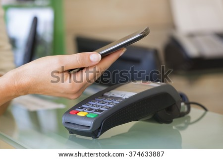 Woman paying with NFC technology on mobile phone, beautician, shop, market - stock photo