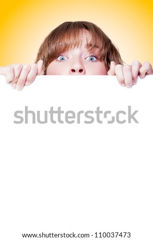 Woman peeking over a blank white placard with just her eyes visible as she draws your attention to the blank copyspace below - stock photo