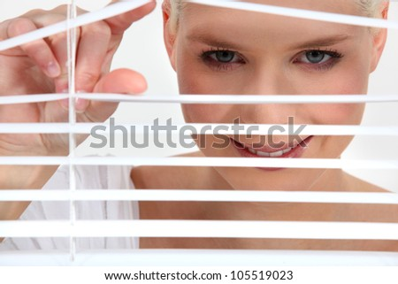 Woman peering through blinds - stock photo