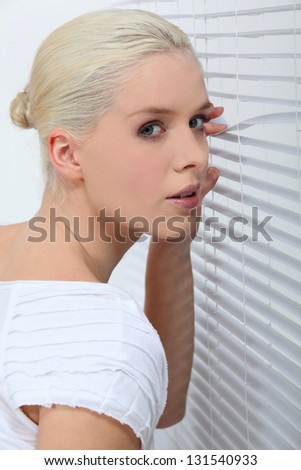 Woman peering through some blinds - stock photo