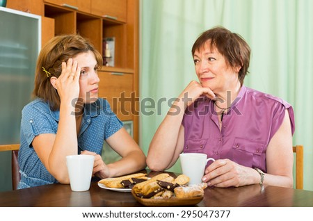 Woman pensioner having conversation with her daughter during coffee - stock photo