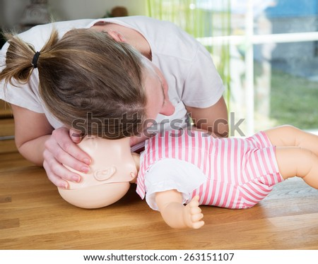 Woman performing CPR on baby training doll, checking for signs of breathing - stock photo