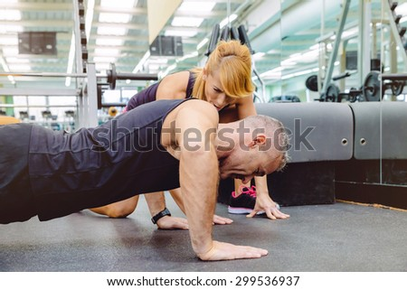 Woman personal trainer encouraging to muscle man during a hard push ups training day on fitness center - stock photo