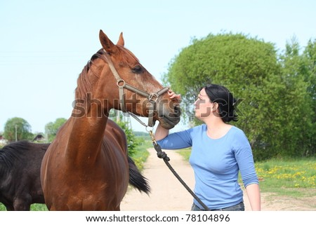 Woman petting brown horse - stock photo