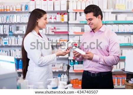 Woman pharmacist counseling customer about drugs usage in modern farmacy - stock photo