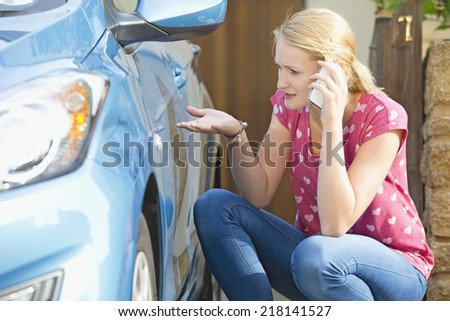 Woman Phoning Insurance Company To Report Car Damage - stock photo