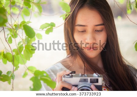 Woman photographer holding film camera in the park - stock photo