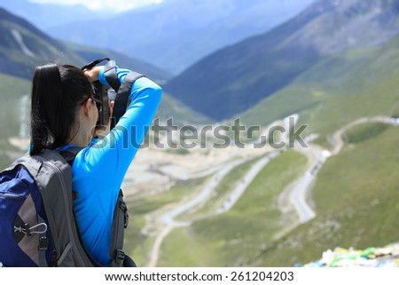 woman photographer taking photo at plateau mountain peak in tibet,china  - stock photo