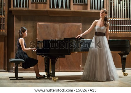 Woman pianist plays the piano and beautiful singer stands next - stock photo