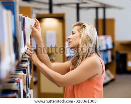 Woman picking a book in public library - stock photo