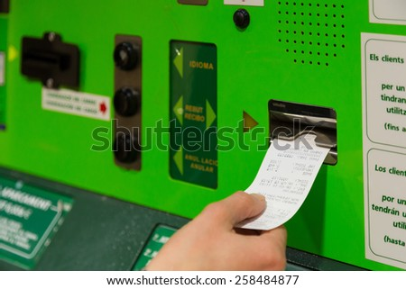 Woman picking the parking ticket to exit - stock photo