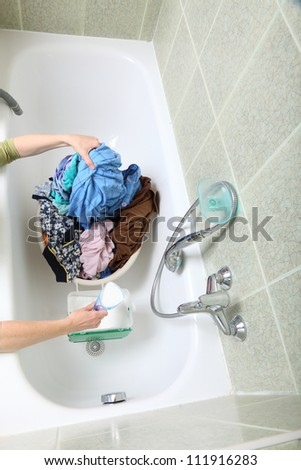 woman Pile of dirty laundry in bath washing machine green bathroom - stock photo