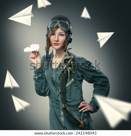 Woman pilot, playing with paper airplanes. - stock photo