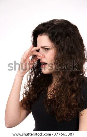 Woman pinches her nose in response to a stinky and smelly odor. - stock photo