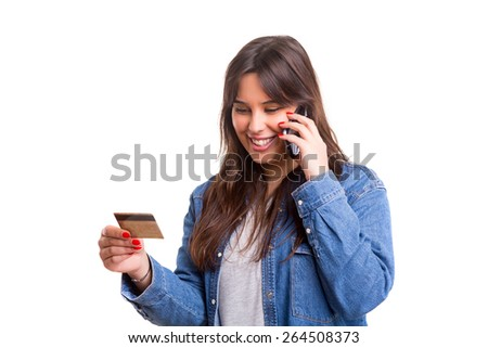 Woman placing an order at the phone with her credit card - stock photo