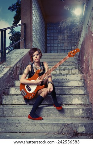Woman player posing on street city location for stylish musician portraits - stock photo