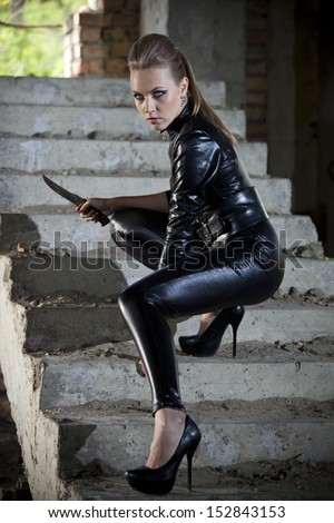 woman playing a spy in leather catsuit, holding a combat knife in fighting pose on stairs - stock photo