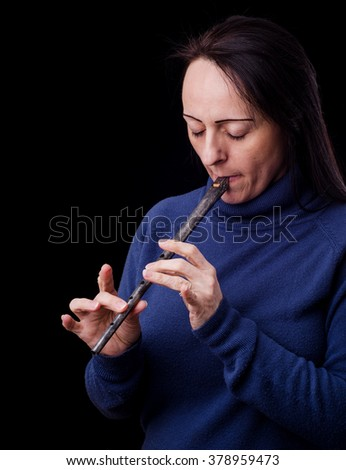 Woman playing a Tin Whistle against black background. - stock photo