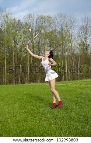 Woman playing badminton game in the park - stock photo