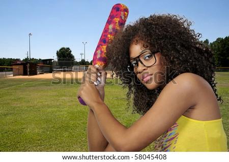Woman playing baseball at a community park - stock photo