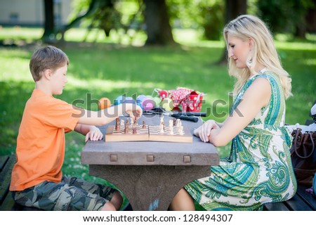 Woman playing Chess with her Son in a Park - stock photo