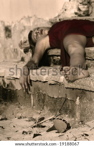 woman playing dead, lying on the stairs - stock photo