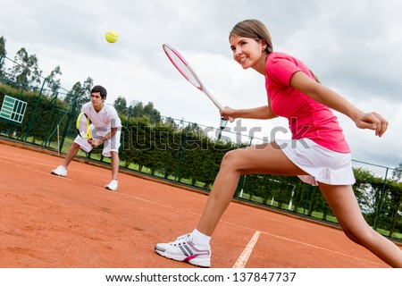 Woman playing doubles in tennis at a clay court - stock photo