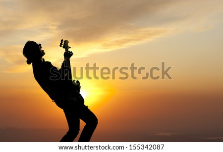 Woman playing guitar against the background of sunset - stock photo